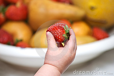 Baby s hand with strawberry