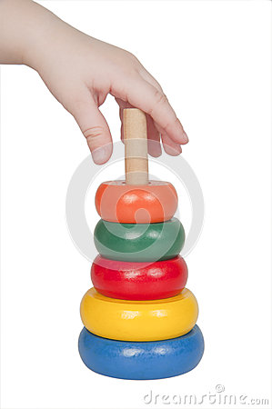 Baby`s hand with wooden toy pyramid isolated