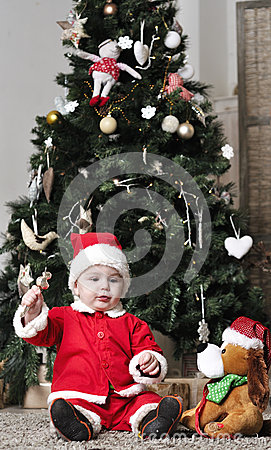 Baby in Santa costume sit near decorating Christmas tree with toy