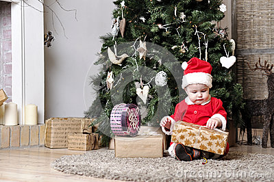 Baby in Santa costume sit near decorating Christmas tree and try unwrap present box