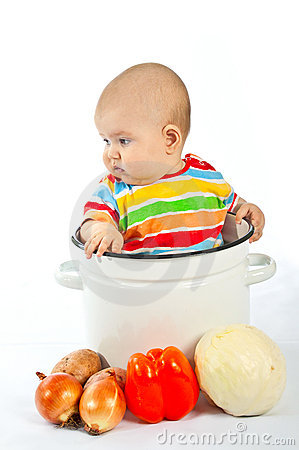 Baby sitting in the big saucepan with vegetables.