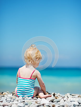 Baby sitting on sea shore
