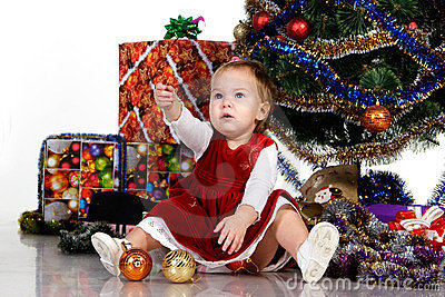 Baby sitting under a Christmas tree