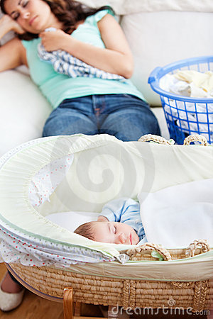 Baby sleeping in his cradle with mother on couch
