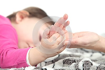 Baby sleeping takes the hand of her mother