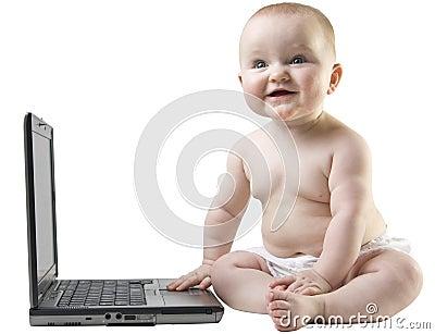 Baby smileing next to laptop.