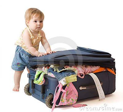 Baby standing near suitcase
