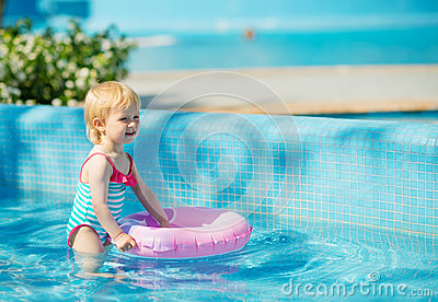 Baby standing in pool with inflatable ring