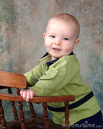 Baby Standing by Wooden Chair