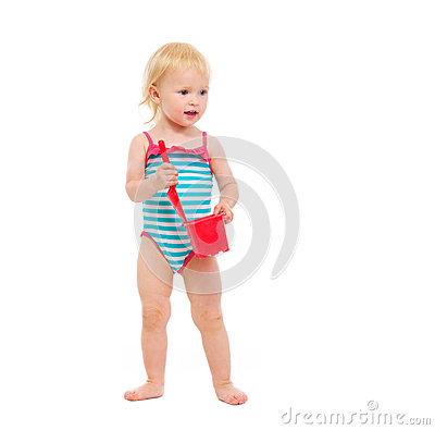 Baby in swimsuit holding bucket and shovel