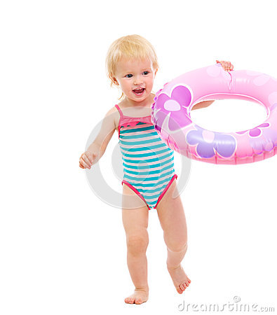Baby in swimsuit playing with inflatable ring
