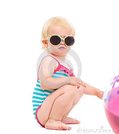 Baby in swimsuit and sunglasses playing with ball