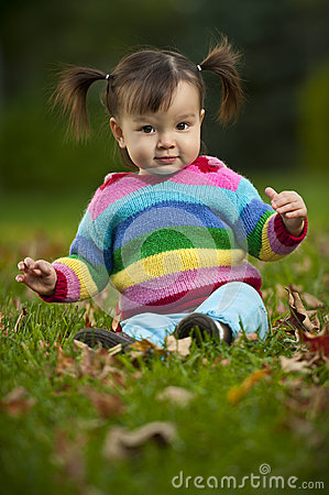 Baby toddler sitting on grass in fall season