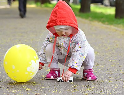 Baby with the toy and baloon