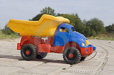 Baby toy dump truck on sunny road