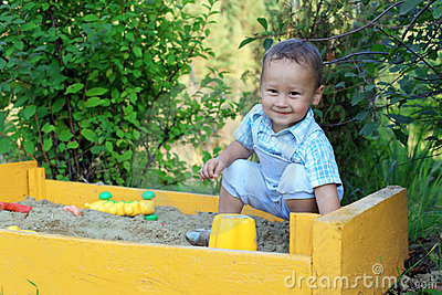 Baby with toys in sandbox