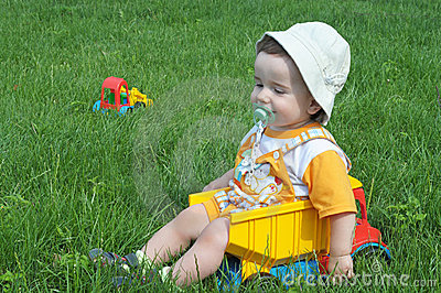 A baby in the truck on the grass