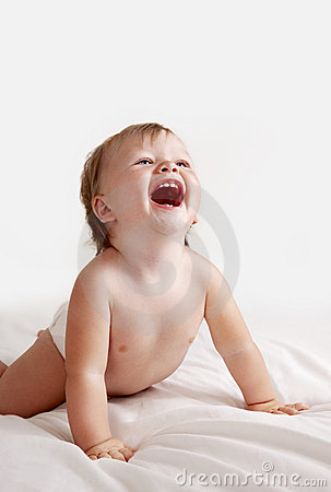 Baby in white sheets laughing