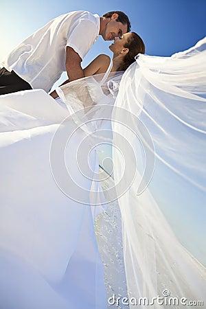Bacio della coppia sposata dello sposo & della sposa alla cerimonia nuziale di spiaggia