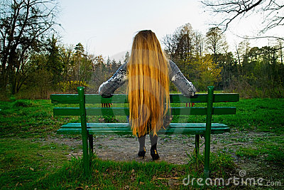 Back of blond hair woman sitting on park bench
