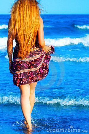 Back of blonde sexy woman walking into the sea