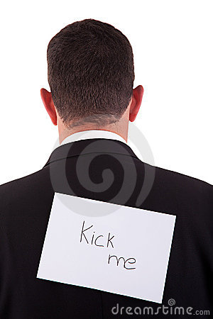 Back of businessman, with kick me written in paper