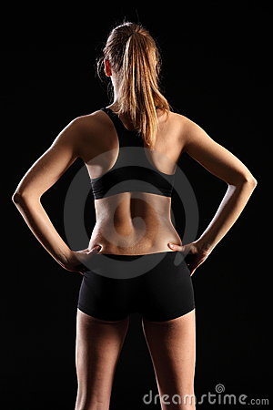 Back of fit young woman in black sports outfit