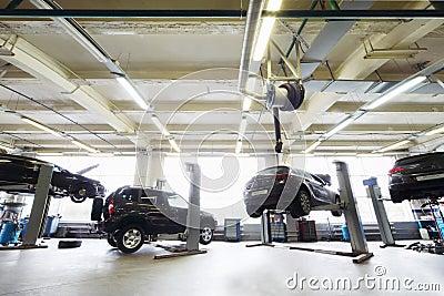Back of four black cars in garage