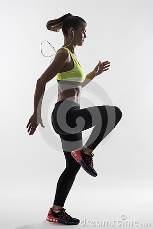 Free Back Lit Silhouette Of Female Runner In Yellow Tank Top Doing High Knees Exercise Stock Photo - 97915280