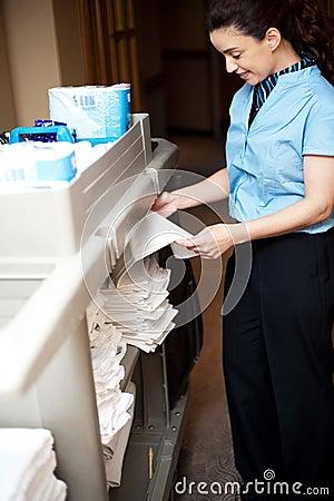 Back-office female employee folding sheets