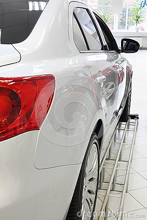 Back red lights of new white shining car standing in office