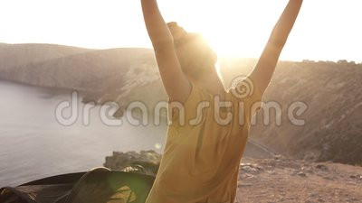 Back side scene of female camper in yellow T shirt spreads her hands and welcomes morning sun. Waked up, comes out from. The tent and standing on a hill against stock video footage