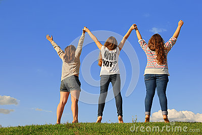 Back of three girls holding hands at grass