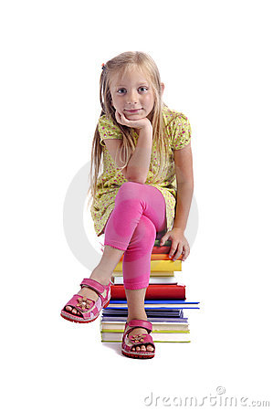 Back to school. Girl sitting on a stack of books