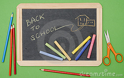 Back to school message on chalkboard with supplies