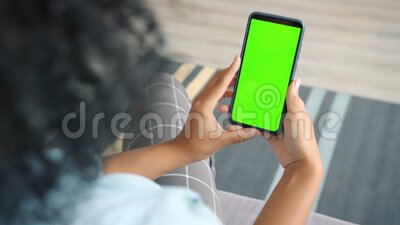 Back view of brunette holding chroma key green screen smartphone watching content. Without touching or swiping. Gadgets and contemporary people concept stock video