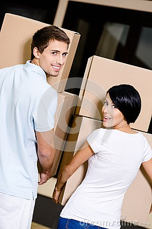 Back view of couple carrying cardboard packages