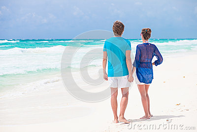 Back view of couple holding hands on tropical