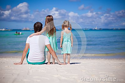 Back view of happy father with his two daughters