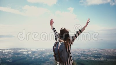 Back view happy female travel blogger with flying hair coming up to epic mountain top scenery on Vesuvius arms wide open. Excited tourist girl smiling