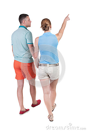 Free Back View Of Walking Young Couple (man And Woman) Pointing. Stock Photos - 44216713