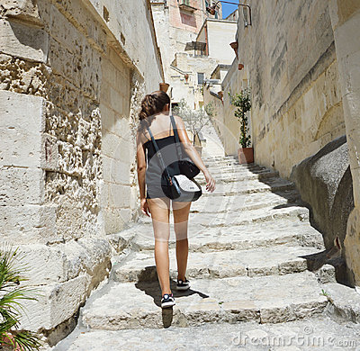Free Back View Of Young Woman Climbing In To The Old Town Of Matera. Attractive Traveller Girl Visit Sassi Di Matera. Female In Typical Stock Photos - 98003813
