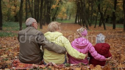 Multi-generation family embracing in autumn park stock video