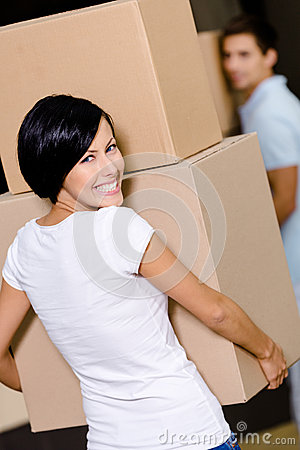 Back view of woman carrying cardboard boxes
