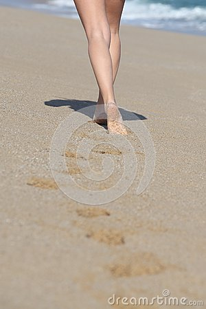 Back view of a woman legs walking on the beach and her traces