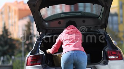 Back view of woman putting shopping bags in car stock footage