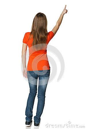 Back view of young casual female in full length pointing at blank copy space