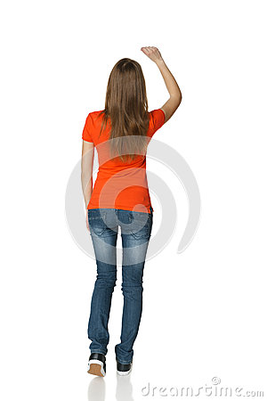 Back view of young casual female in full length writing on the blank copy space