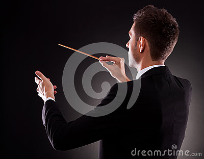 Back view of a young composer directing
