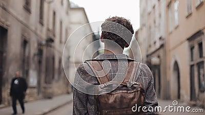 Back View Young Tourist Guy con zaino marrone e auricolari con la giacca selezionata che passeggiava per Old City Street archivi video